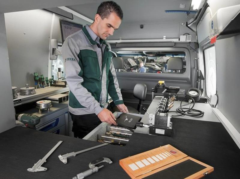 Mann mit DEKRA-Jacke und Werkzeug