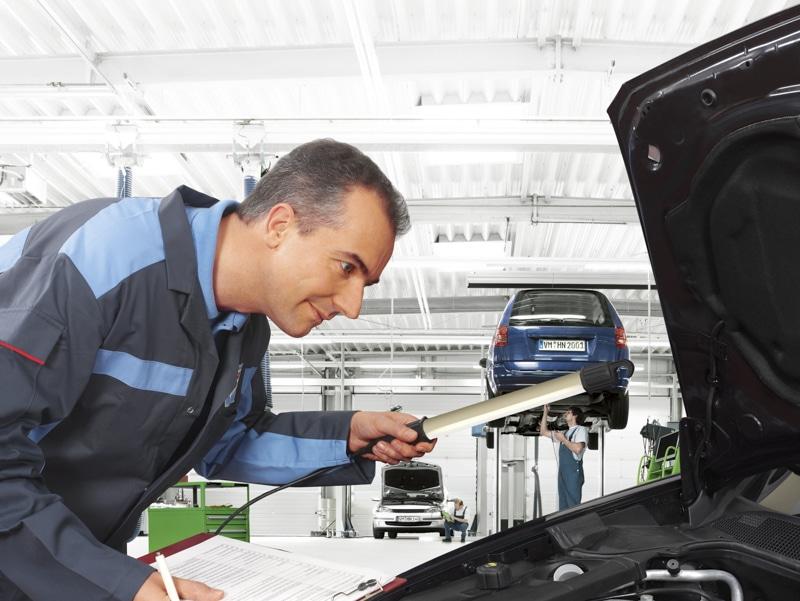 BOSCH Servicemitarbeiter untersucht die Motorhaube eines PKW