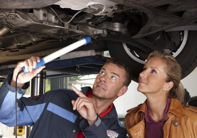 BOSCH Servicemitarbeiter zeigt Kundin unter Auto etwas